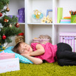 Little girl sleeping near Christmas tree in room — Stock Photo