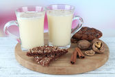 Cups of eggnog with cinnamon and cookies on table on bright background — Stock Photo