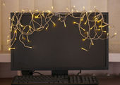 Laptop with garland, on office interior background — Stok fotoğraf