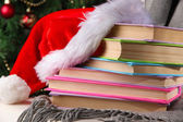 Composition with books and plaid, red hat, on chair on Christmas tree background — Stock Photo