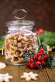 Delicious Christmas cookies in jar on table on brown background — Stockfoto