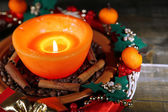 Burning candle with Christmas decorations on color wooden background — Foto Stock