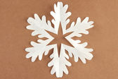 Beautiful paper snowflake on brown background — Stock Photo
