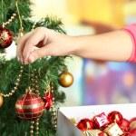 Decorating Christmas tree on bright background — Stock Photo