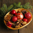 Christmas decorations in basket and spruce branches on wooden background — Stock Photo #37721855