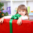 Little girl with big present box near Christmas tree in room — Stock Photo #37722157