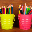 Colorful pencils in two pails on wooden background — Stock Photo #37722765