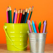 Colorful pencils in two pails on table on orange background — Stock Photo