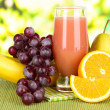 Glass of fresh juice on table on bright background — Stock Photo