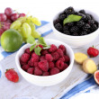 Raspberries and blackberry in small bowls on board on napkin isolated on white — Stock Photo