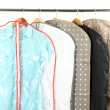 Stock Photo: Clothes in cases for storing on hangers, on gray background