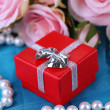 Stock Photo: Rose and gift box on blue cloth