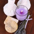 Still life with lavender candle, soap, massage balls, bottles, soap and fresh lavender, on wooden table on wooden background — Stock Photo
