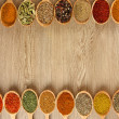 Assortment of spices in wooden spoons on wooden background — Stock Photo #37725663