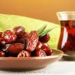 Stock Photo: Dried dates on plate with cup of tea on table on fabric background
