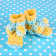 Crocheted booties for baby, on color background — Stock Photo #37728769