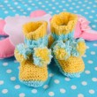 Crocheted booties for baby, on color background — Stock Photo #37728773