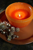 Burning candle with Christmas decorations on color plate, on wooden background — 图库照片