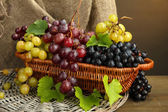 Assortment of ripe sweet grapes in basket, on burlap background — Stock Photo