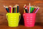 Lápis coloridos em dois baldes em fundo de madeira — Fotografia Stock