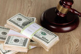 Stacks of money and judges gavel on wooden table — Stockfoto