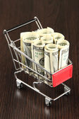 Shopping trolley with dollars, on dark background — Photo