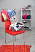 Heap of clothes on color chair, on gray background — ストック写真