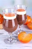 Dessert of chocolate and persimmon on table on light background — Stock Photo