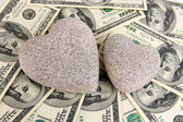 Love and money concept. Heart-shaped stone and American currency close up. — Stock Photo
