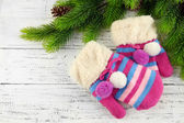 Striped mittens with fir branches on wooden background — Stock Photo