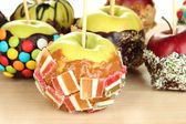 Candied apples on sticks on wooden table close up — Stock Photo