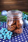 Delicious Christmas cookies in jar on table on wooden background — Stock Photo