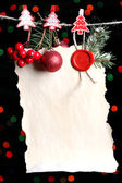 Blank sheet with Christmas decor on black background with lights — Foto Stock
