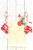 Blank sheet with Christmas decor hanging on white wooden wall — Stock Photo