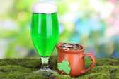 Glass of green beer and pitcher with coins on grass on natural background — Stock Photo
