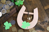 Chest with coins and horseshoe on wooden table close-up — Stock Photo
