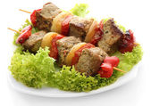 Tasty grilled meat and vegetables on skewers on plate, isoalted on white — Stock Photo