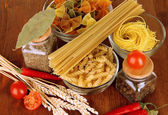 Different types of pasta, spices, tomatoes on a wooden table — Stock Photo