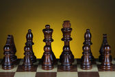 Chess board with chess pieces on dark color background — Foto de Stock