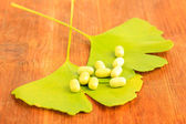 Ginkgo biloba leaves and pills on wooden background — Stockfoto