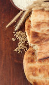 Pita breads with spikes and flour on wooden background — Stock Photo