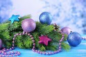 Christmas balls on fir tree, on color background — Stock Photo