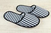 Striped slippers on wooden background — Zdjęcie stockowe