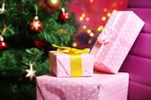 Christmas gift boxes on Christmas tree background — Stock Photo