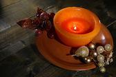 Горящая свеча с рождественские украшения на цветовой пластине, на фоне деревянных — Стоковое фото