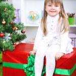 Little girl setting on big present box near Christmas tree in room — Stock Photo #37780261