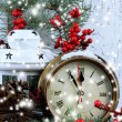 Clock with fir branches and Christmas decorations on table on wooden background — Stock Photo #37780809