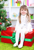 Little girl setting on big present box near Christmas tree in room — Foto Stock
