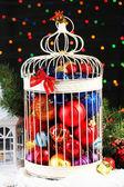 Julgranskulor i dekorativ bur, mot glänsande bakgrund — Stockfoto