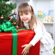 Little girl with big present box near Christmas tree in room — Stock Photo #37798283